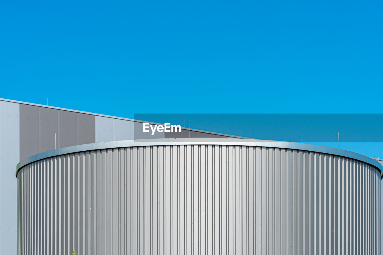 Low angle view of storage tank against clear blue sky