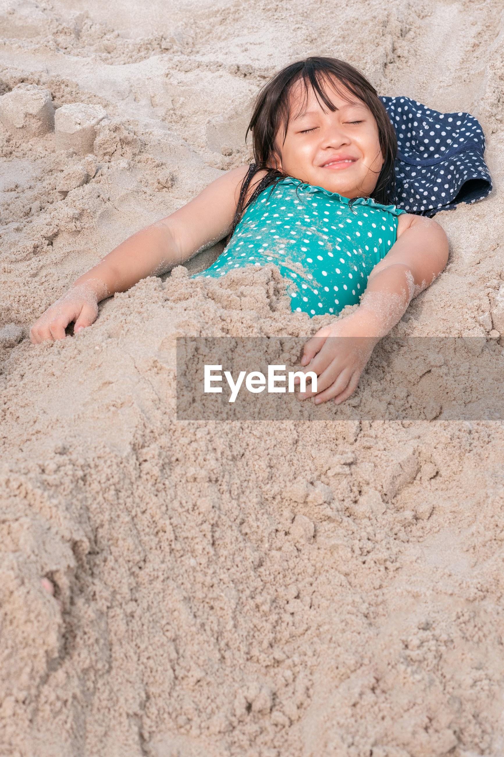 Portrait of girl lying on sand