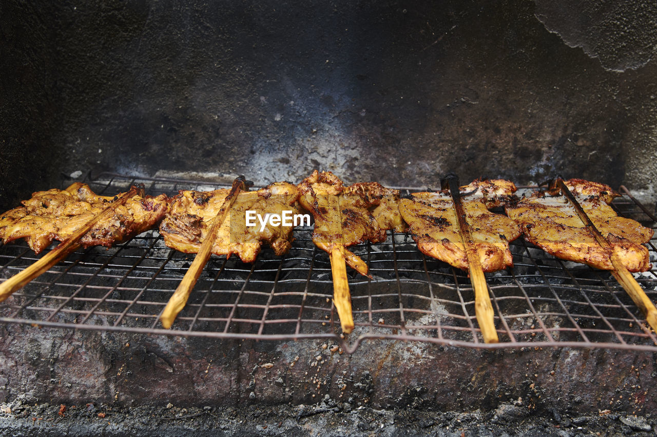 Grilled chickens on metal grate