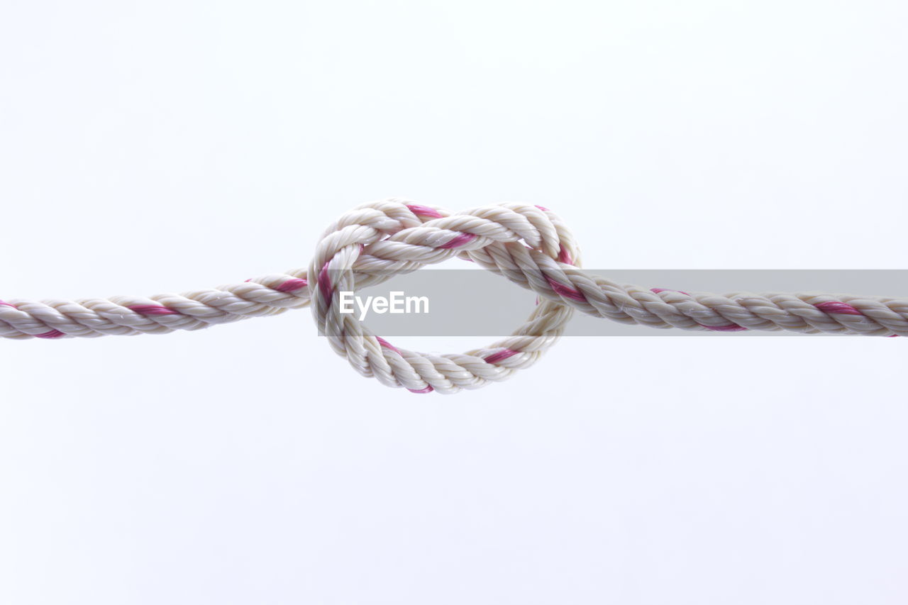 studio shot, white background, copy space, rope, close-up, indoors, strength, string, cut out, no people, tied knot, tied up, still life, heart shape, single object, intertwined, connection, pattern, jewelry, twisted, tangled, personal accessory