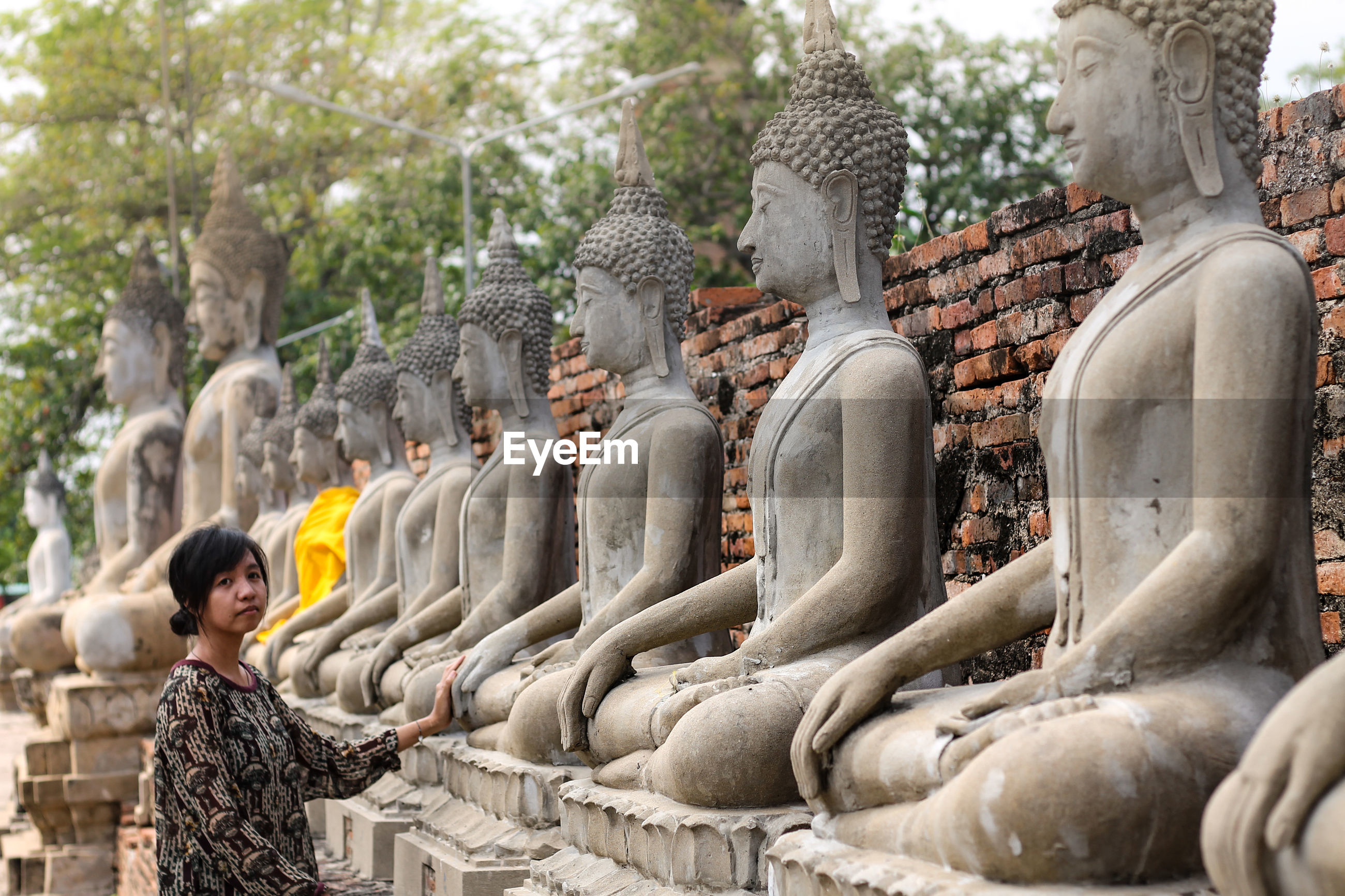 Portrait of mid adult woman standing by buddha statues