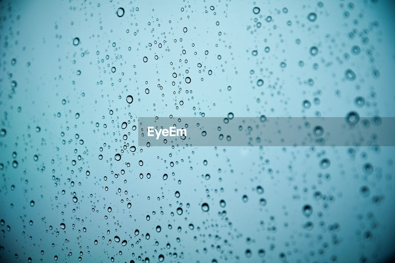 Full Frame Shot Of Water Drops On Glass Window During Monsoon