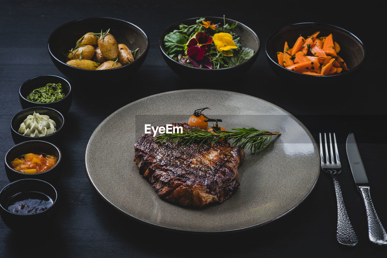 food, food and drink, freshness, ready-to-eat, vegetable, meat, plate, kitchen utensil, table, fork, indoors, eating utensil, healthy eating, meal, still life, serving size, red meat, high angle view, bowl, no people, beef, table knife, glass, garnish, dinner, temptation