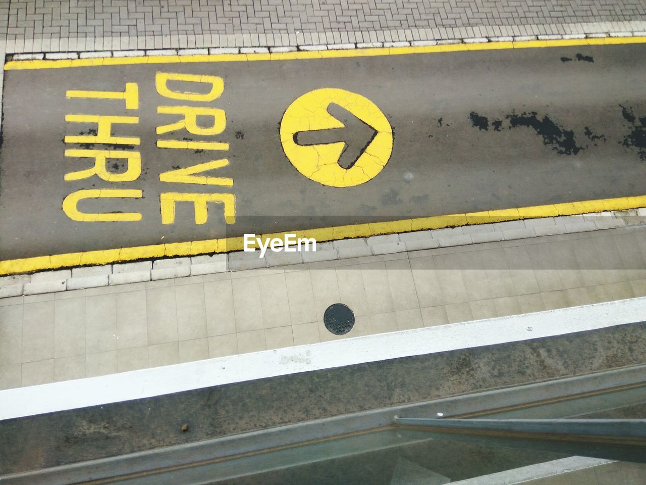 yellow, sign, communication, high angle view, no people, text, transportation, western script, day, architecture, outdoors, number, marking, close-up, road, metal, symbol, guidance, information