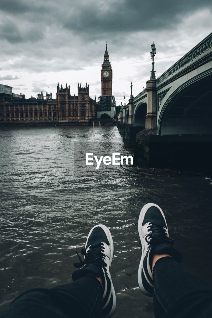 Low section of man by river against big ben