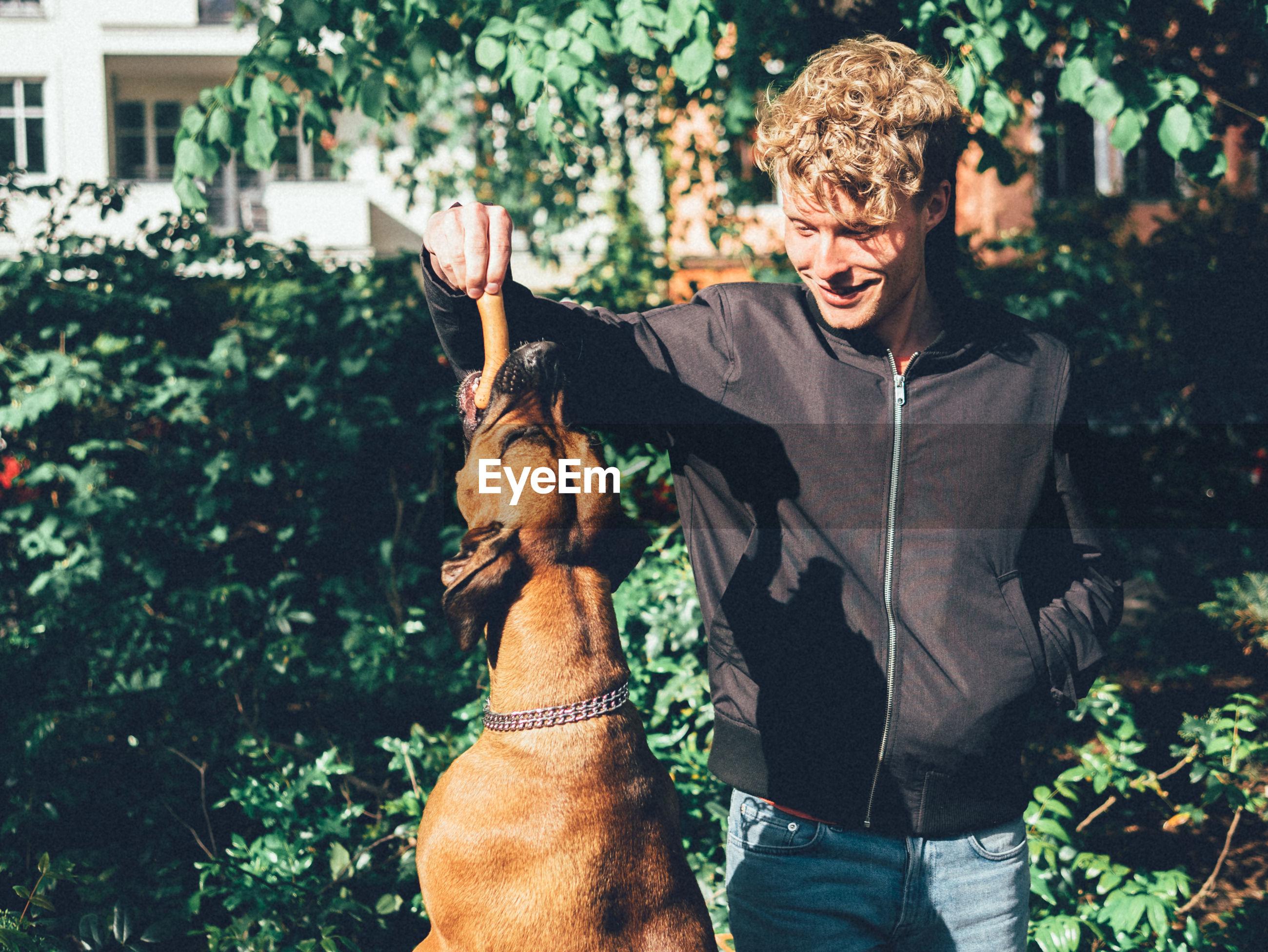 Smiling young man feeding sausage to dog in yard