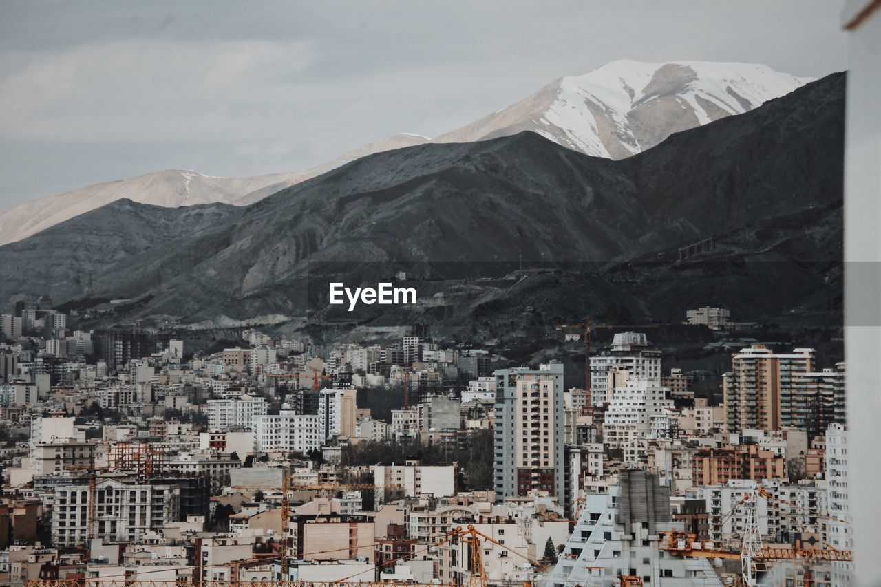 High Angle View Of Buildings By Alborz Mountain Against Sky