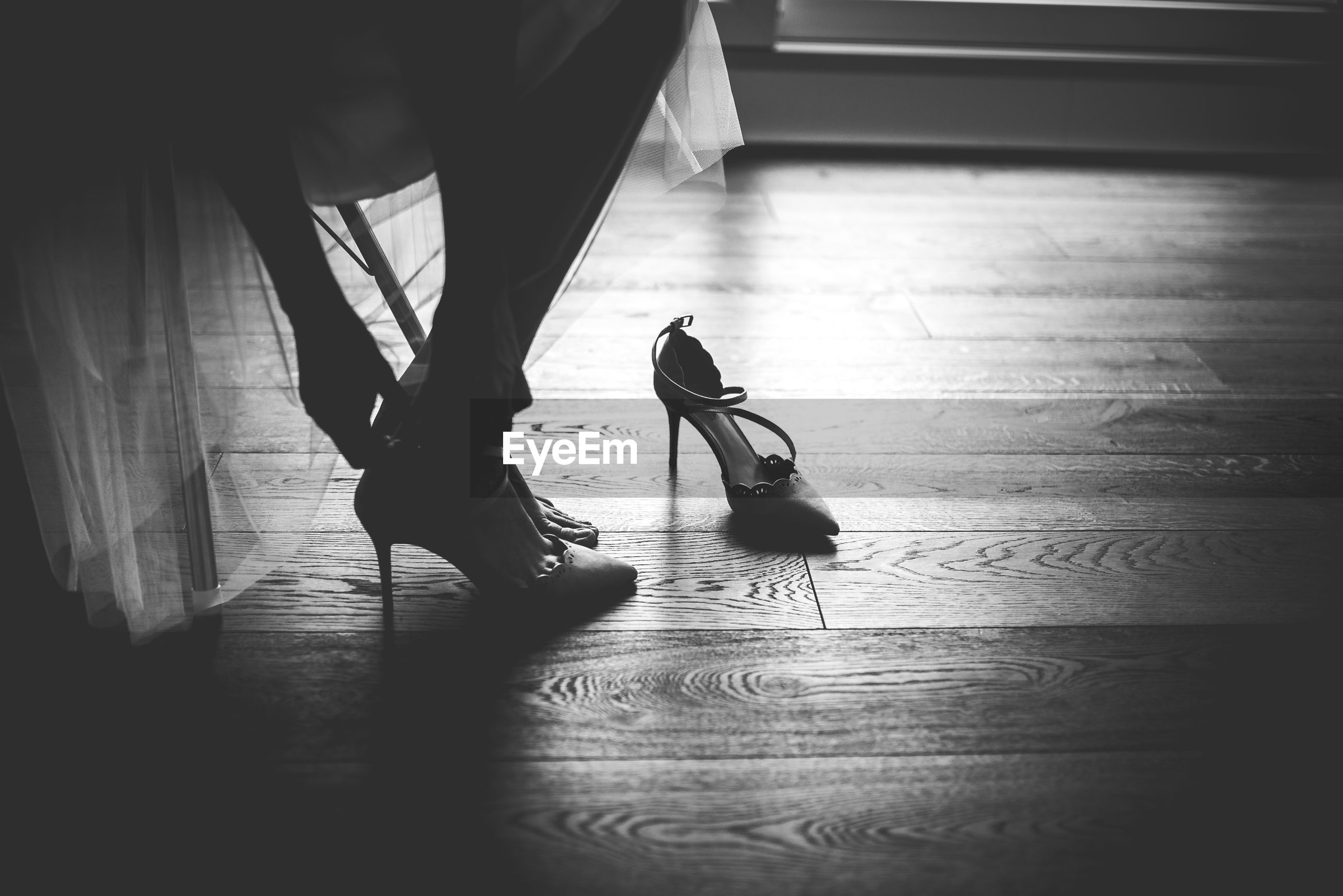 Low section of mid adult woman wearing sandals on hardwood floor