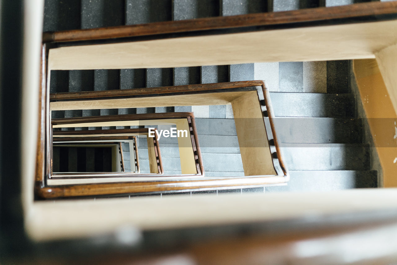 architecture, railing, no people, staircase, wood - material, built structure, indoors, steps and staircases, day, window, spiral, selective focus, metal, directly above, building, spiral staircase, high angle view, pattern, glass - material