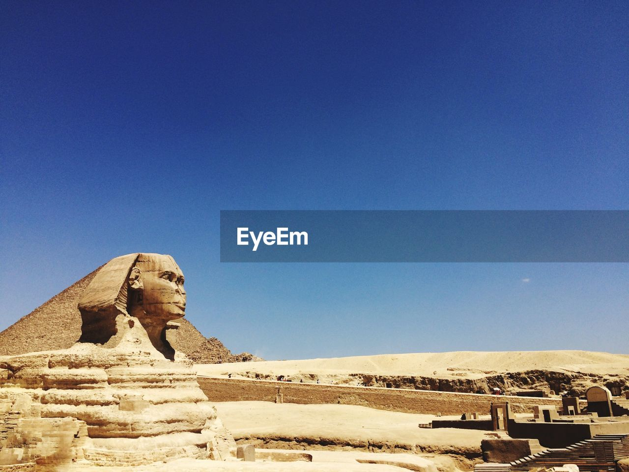 The Great Sphinx And Pyramids Against Clear Blue Sky
