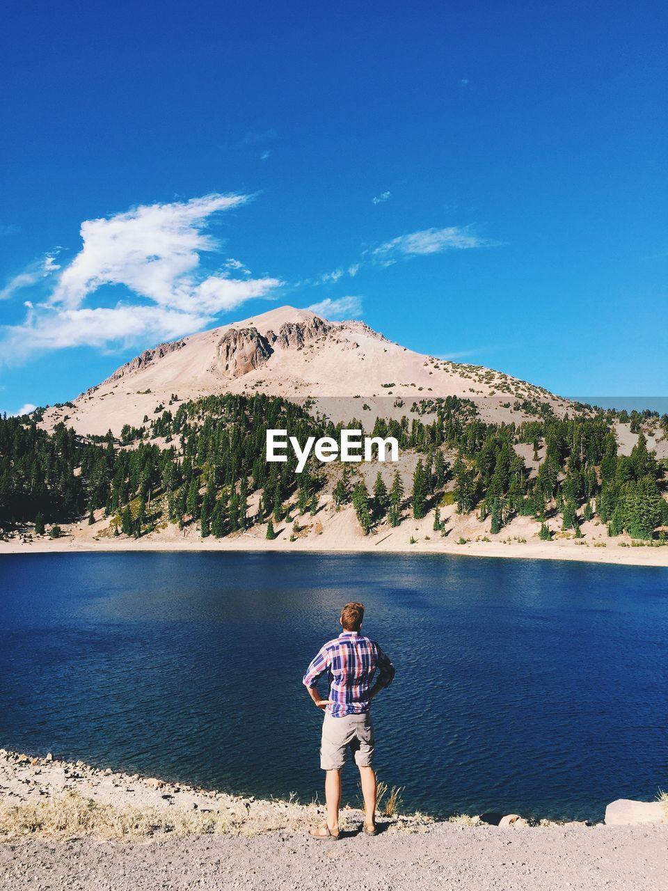 Rear View Of Man Looking At Lake And Mountain Against Sky