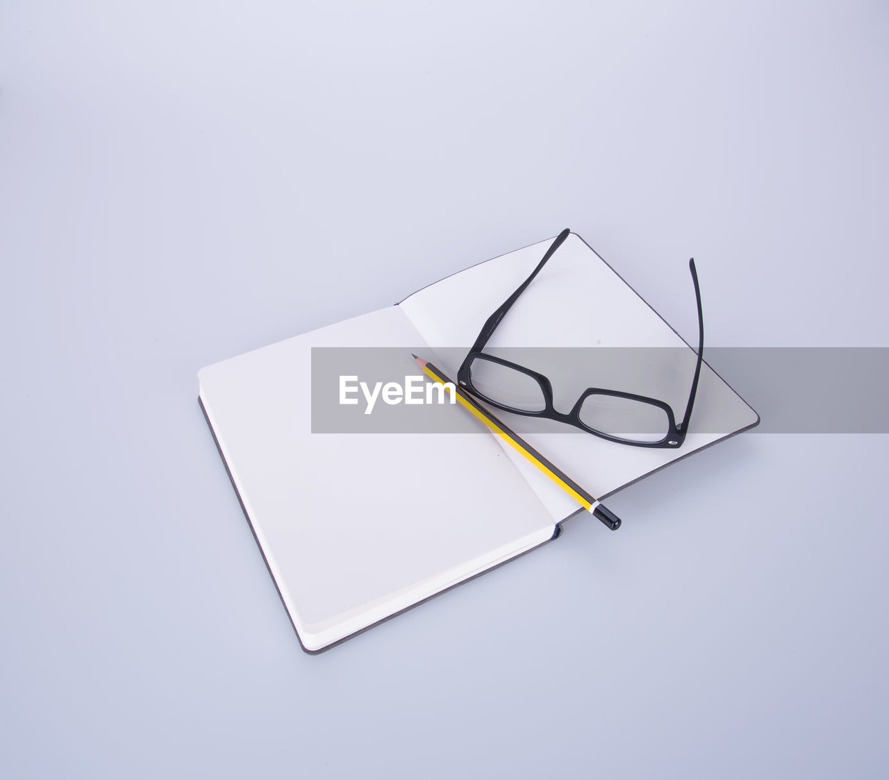 still life, studio shot, copy space, indoors, white background, no people, paper, white color, high angle view, close-up, cut out, book, note pad, table, office supply, eyeglasses, mobile phone, pencil, wireless technology, publication, blank