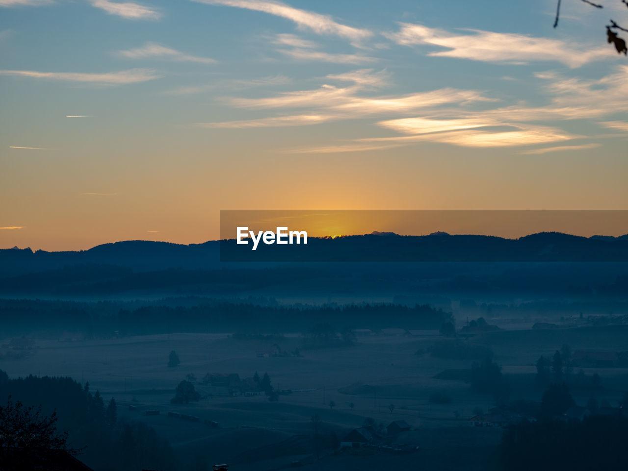 sunset, beauty in nature, sky, scenics - nature, tranquility, tranquil scene, cloud - sky, orange color, idyllic, mountain, nature, silhouette, no people, environment, non-urban scene, outdoors, landscape, mountain range, sun, hazy