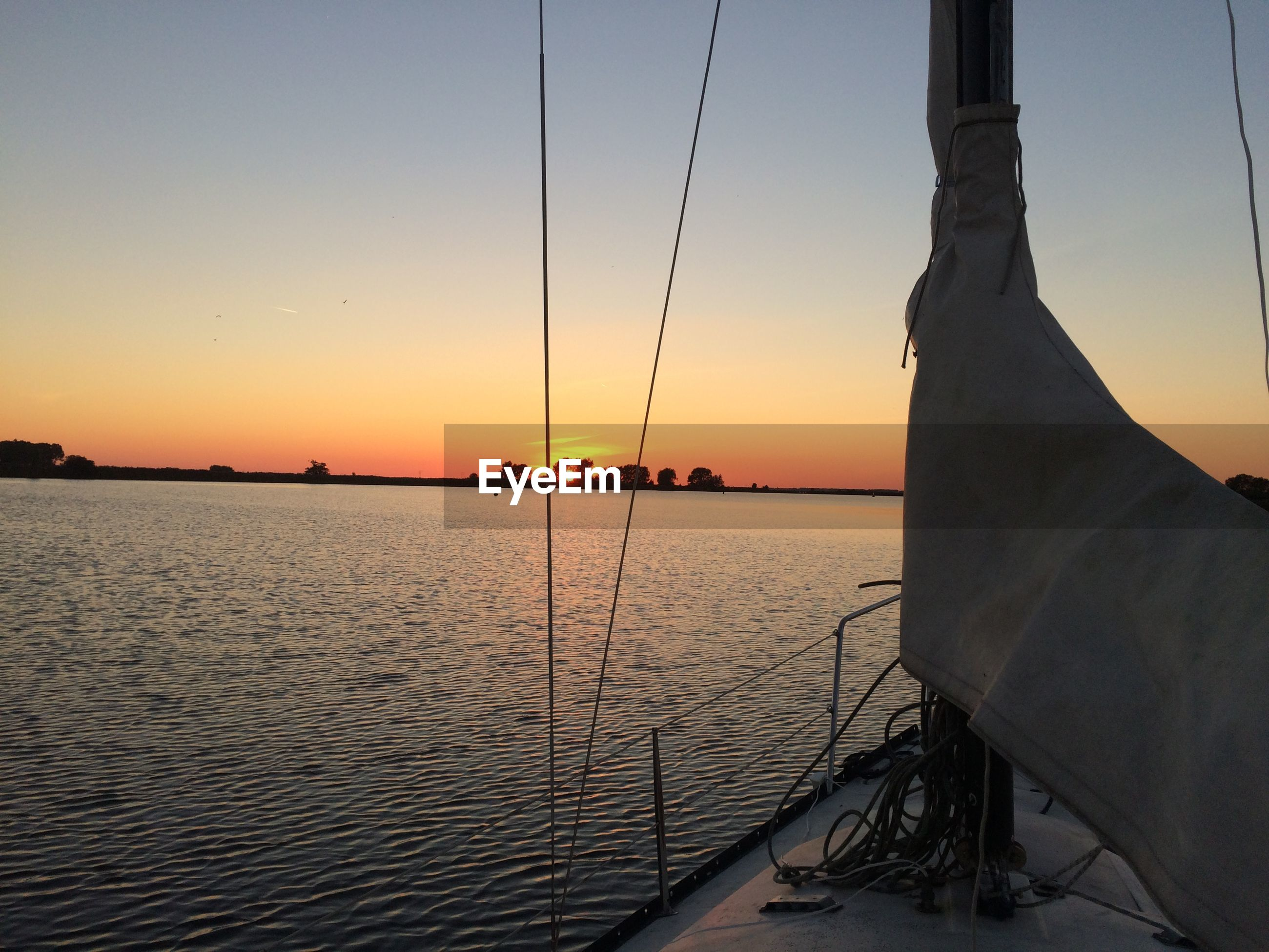 Boat sailing in river against clear sky at sunset