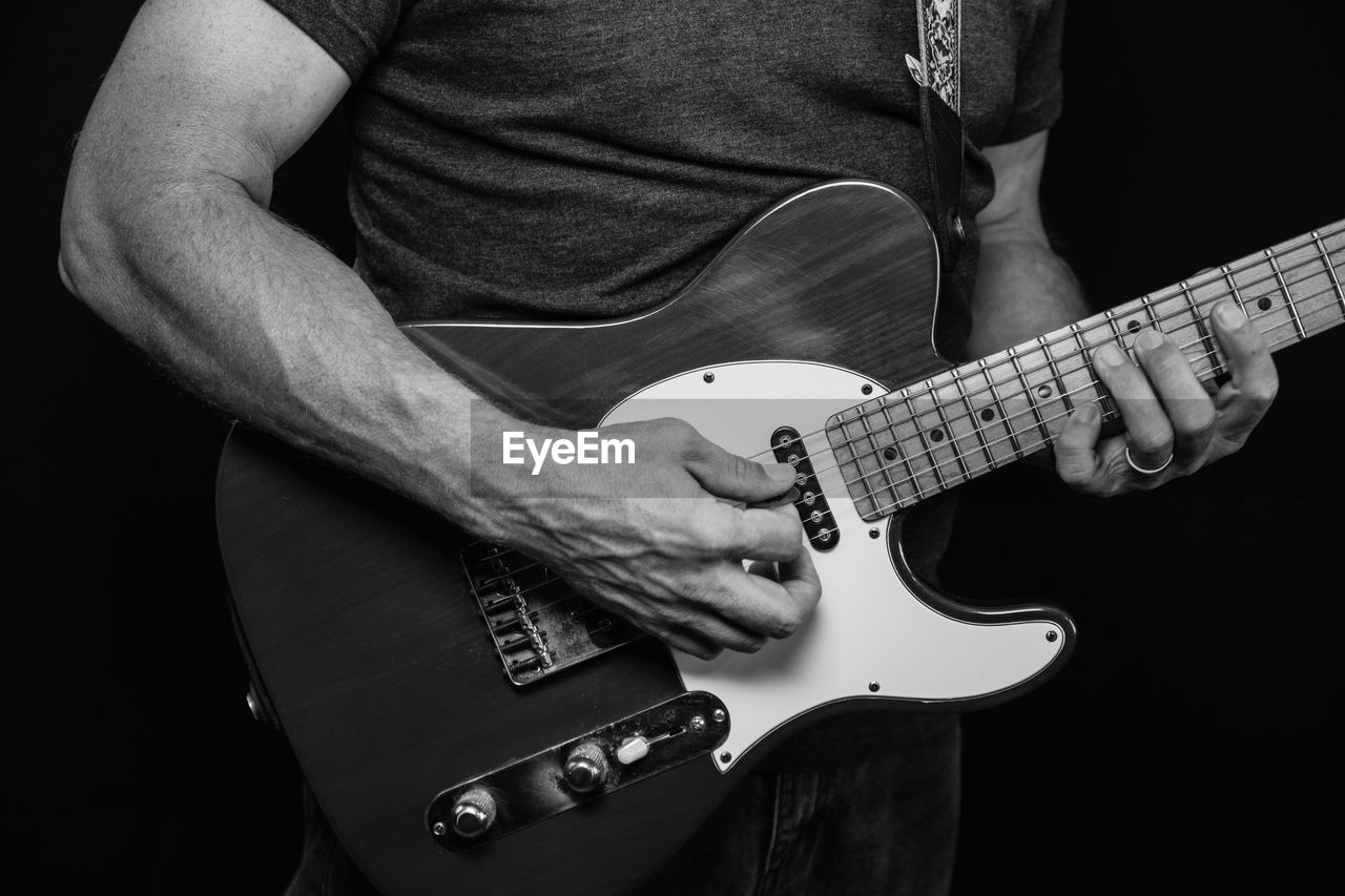 MIDSECTION OF MAN PLAYING GUITAR IN BLACK