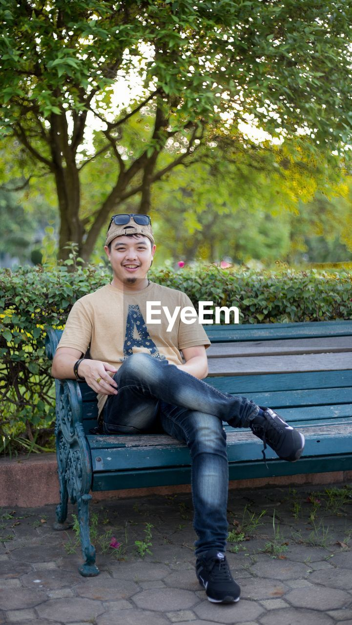 PORTRAIT OF A SMILING YOUNG MAN SITTING ON BENCH IN PARK