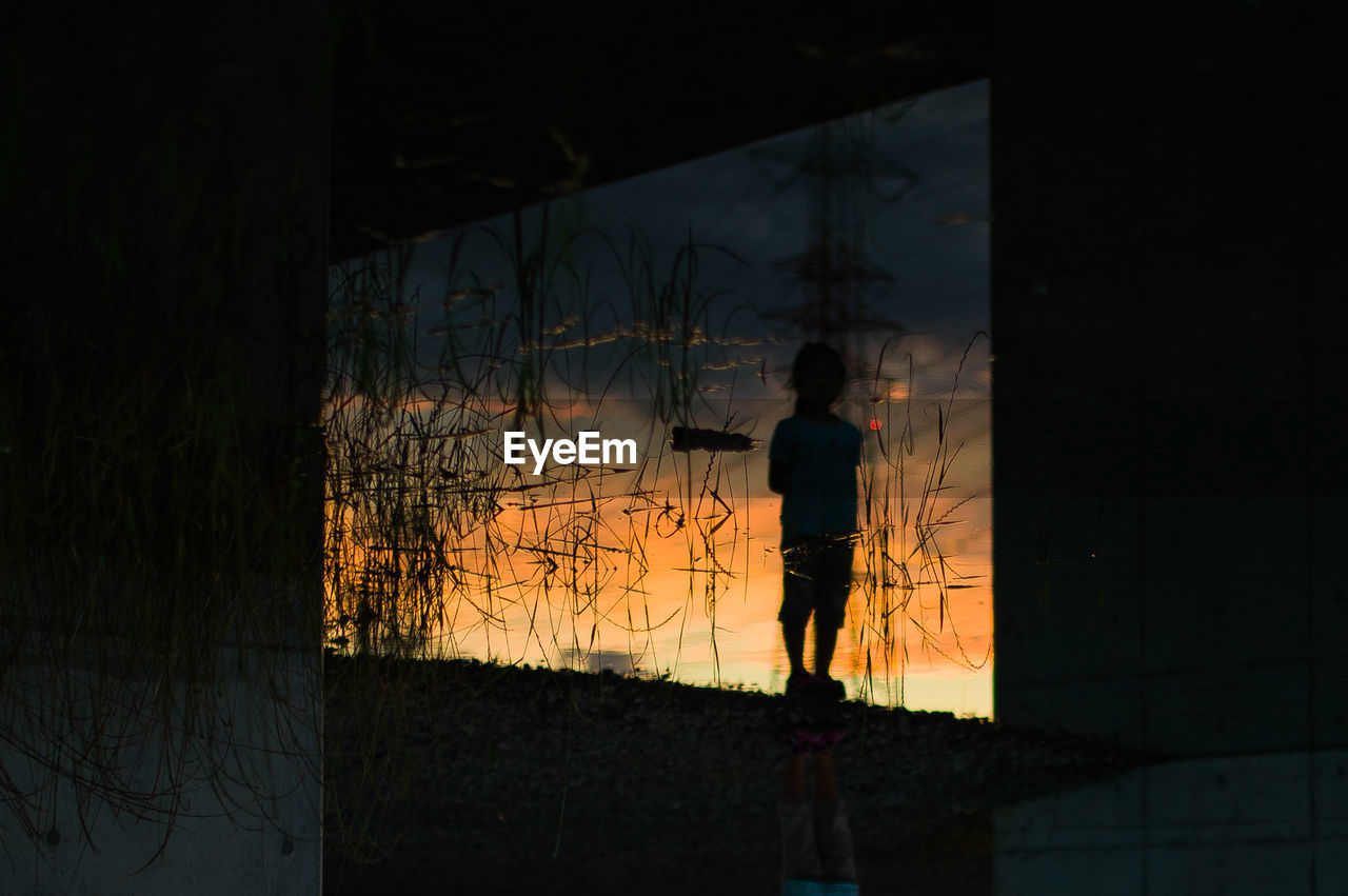 Silhouette boy reflecting on lake during sunset