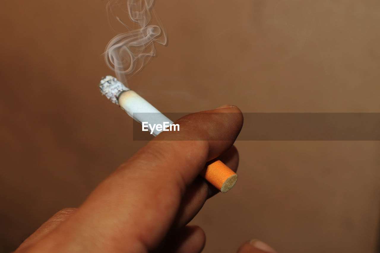 Cropped hand holding cigarette against brown background