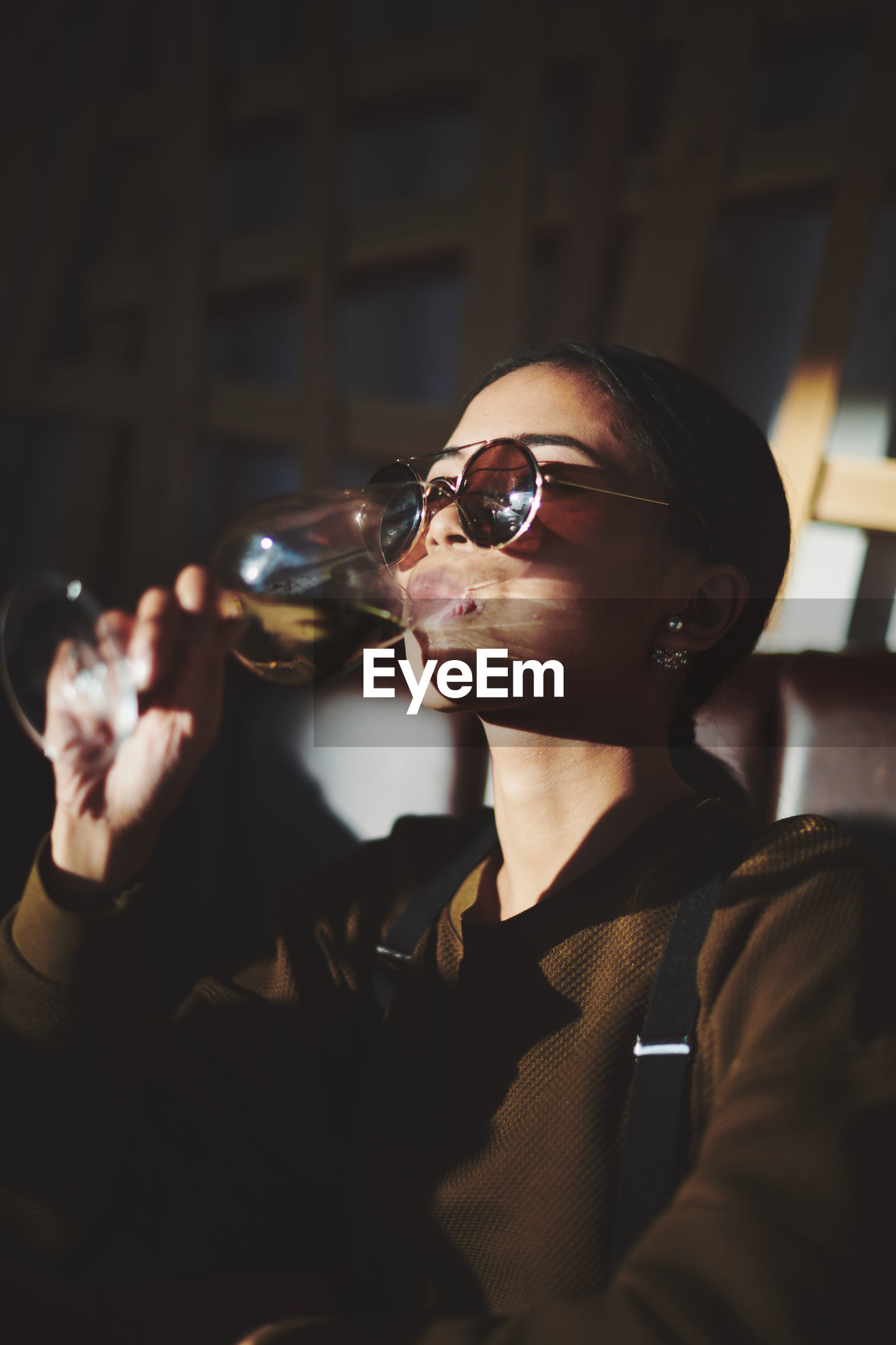 glasses, adult, one person, drink, black, holding, sunglasses, fashion, refreshment, drinking, women, young adult, person, food and drink, lifestyles, portrait, indoors, vision care, alcohol, glass, leisure activity, human face, singing, men, sitting, waist up, clothing, night, goggles, female, looking, eyewear, business
