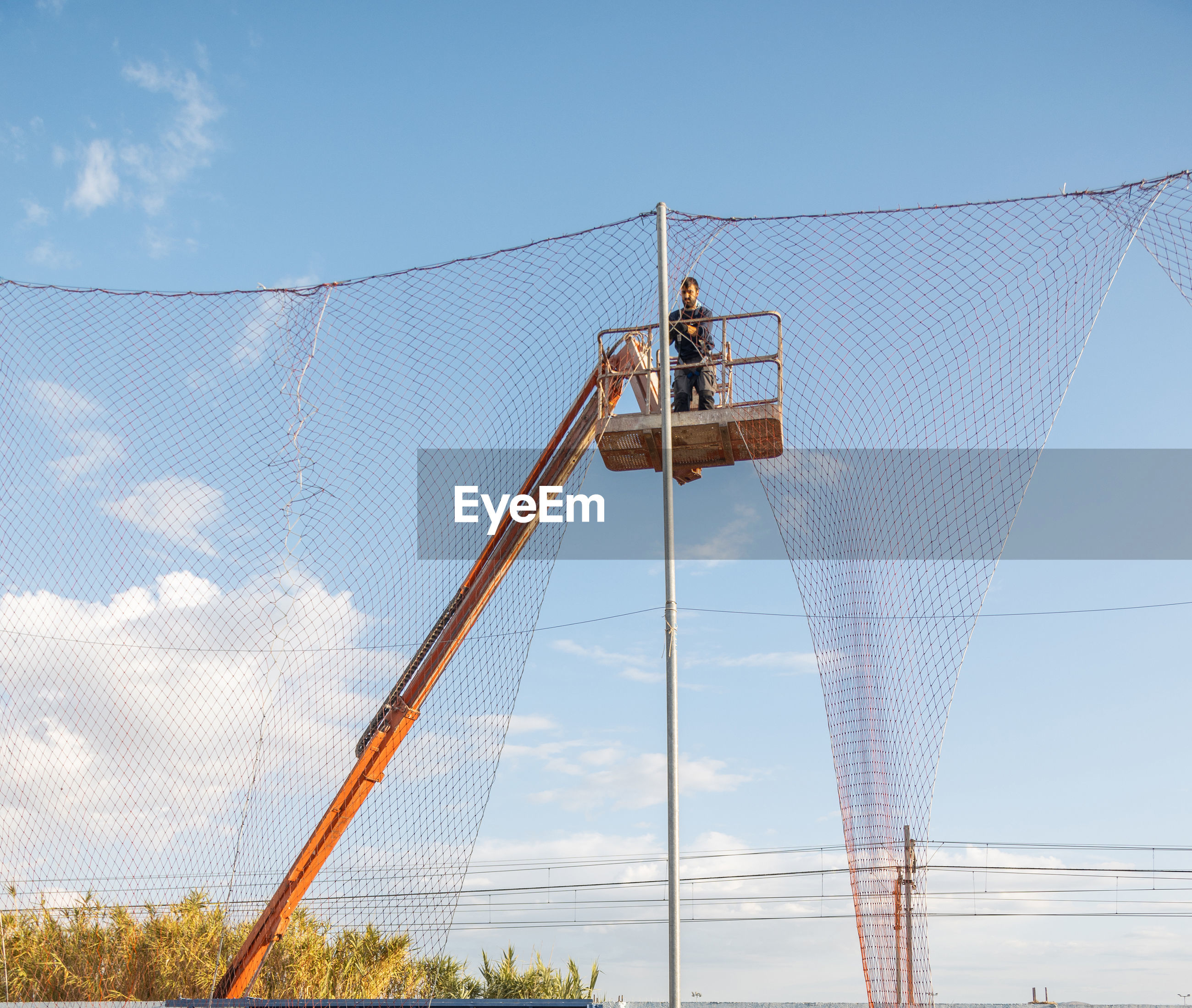 Low angle view of man on crane against sky