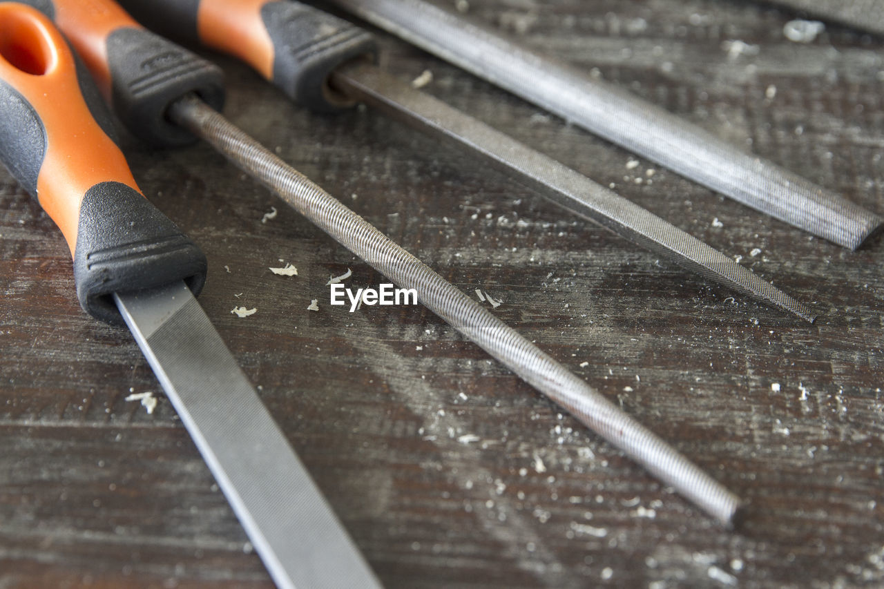 work tool, metal, wood - material, no people, selective focus, indoors, close-up, table, equipment, sharp, blade, still life, instrument of measurement, wet, tool, man made object, hand tool, knife, man made, industry, steel, alloy