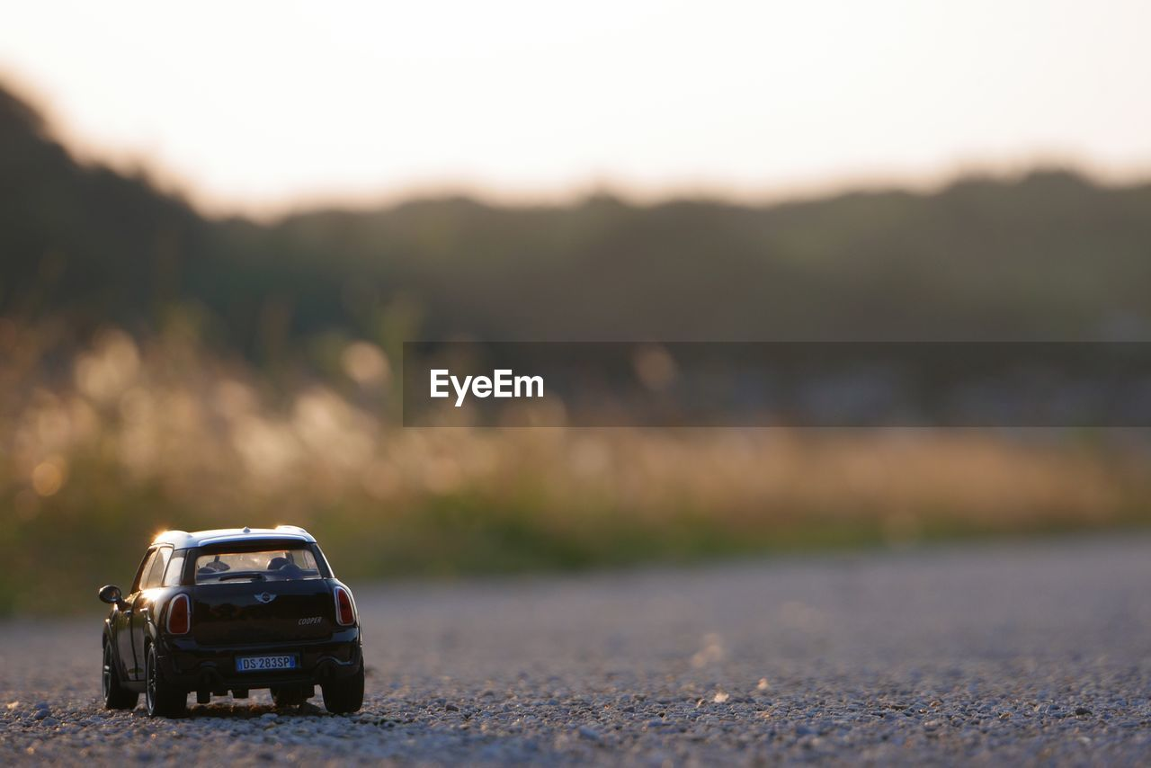 transportation, mode of transportation, car, motor vehicle, land vehicle, road, nature, no people, outdoors, toy car, city, toy, direction, day, sky, on the move, sunset, selective focus, travel, land, road trip