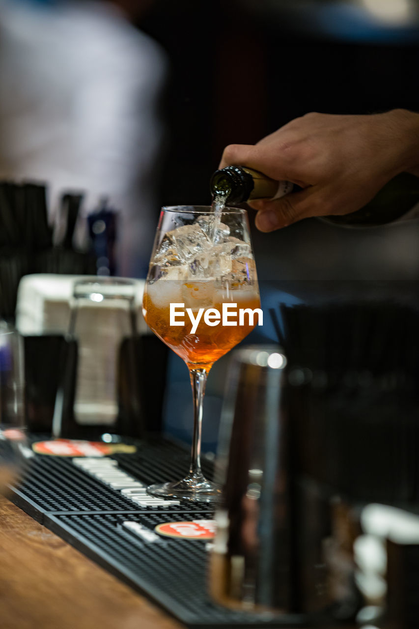 Cropped Hand Of Male Bartender Pouring Alcohol In Wineglass At Bar