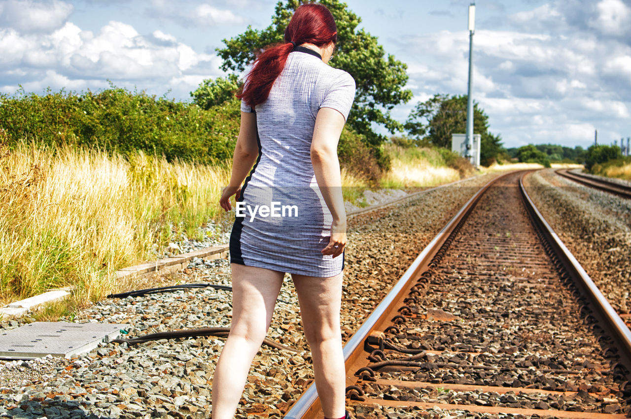 FULL LENGTH REAR VIEW OF WOMAN STANDING ON RAILROAD TRACK