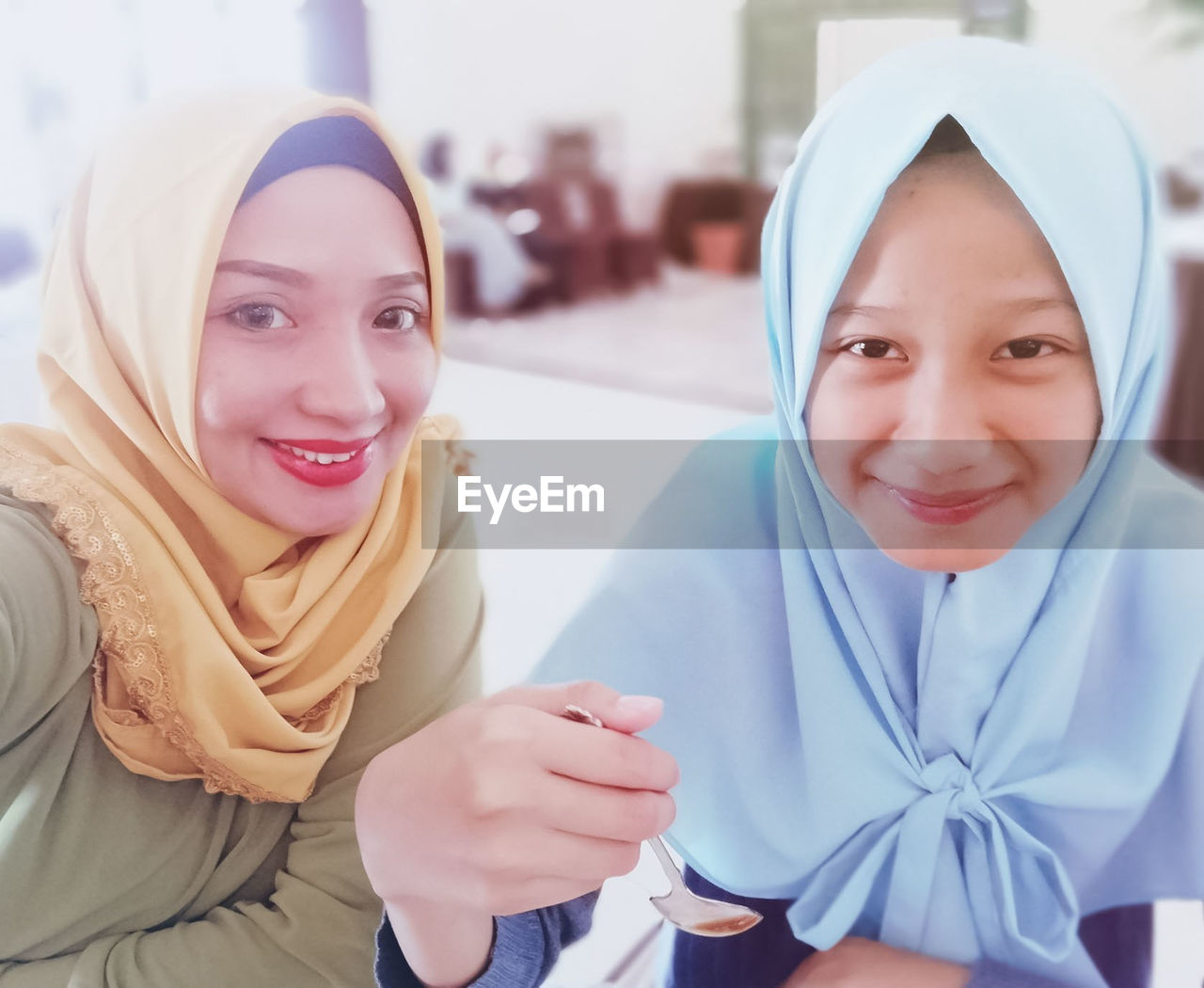 Portrait Of Smiling Sisters Wearing Hijab At Home