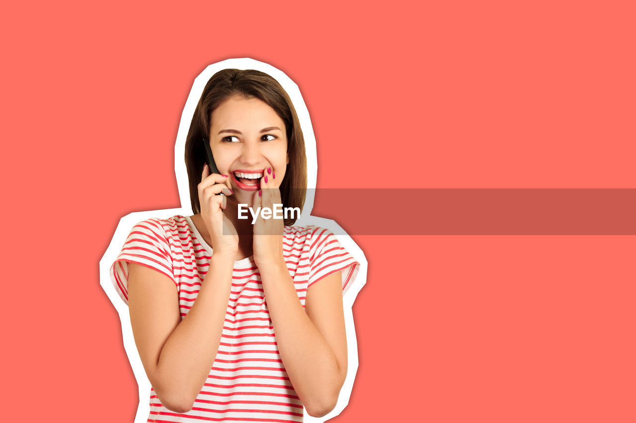 Surprised young woman talking over mobile phone cut out against coral background