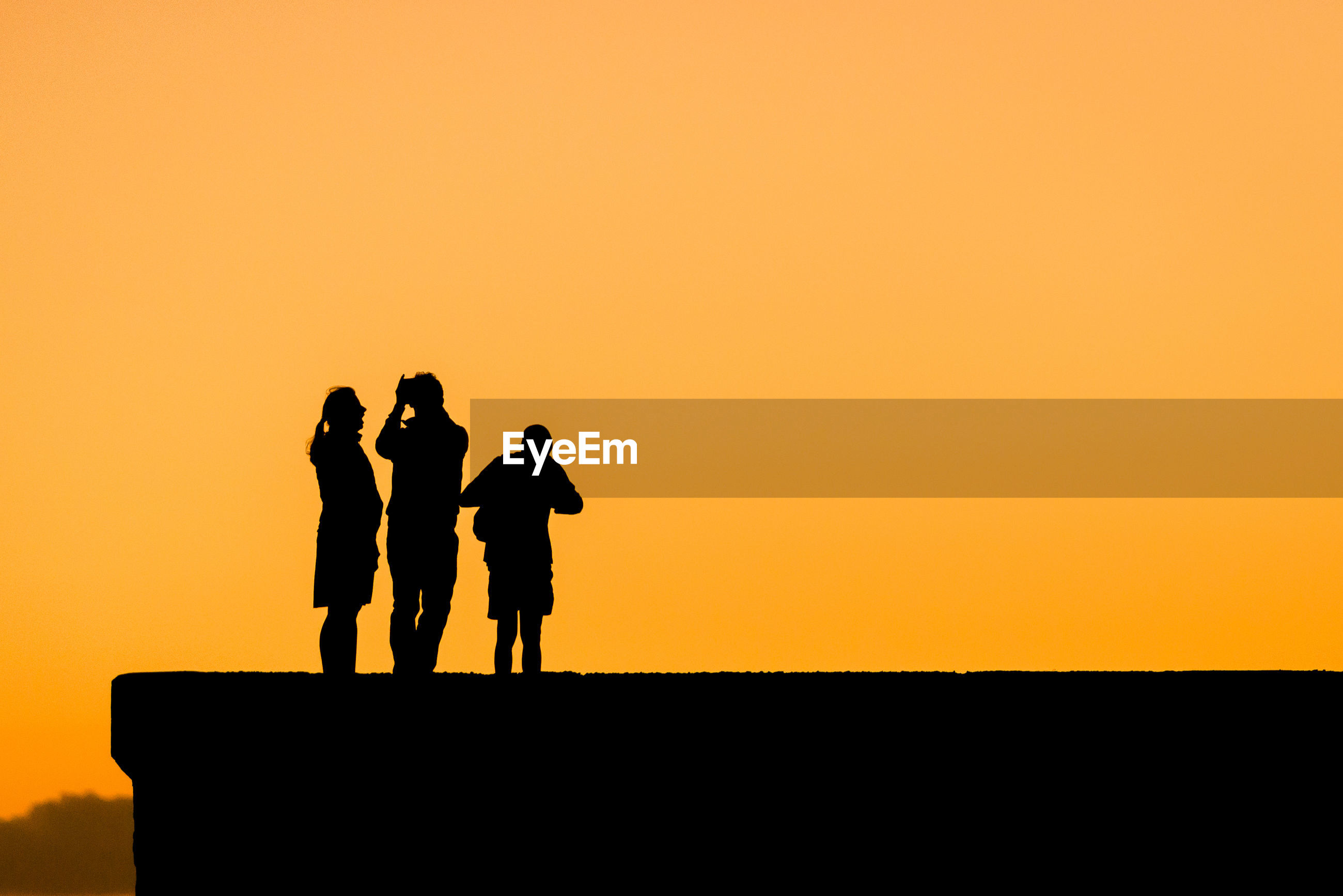 Silhouette people standing against clear sky during sunset