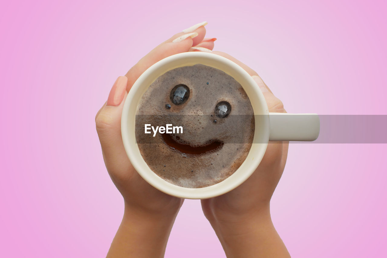 drink, cup, food and drink, mug, refreshment, coffee, indoors, coffee - drink, coffee cup, holding, pink color, studio shot, pink background, freshness, one person, colored background, human body part, close-up, human hand, food, hot drink, frothy drink, hand