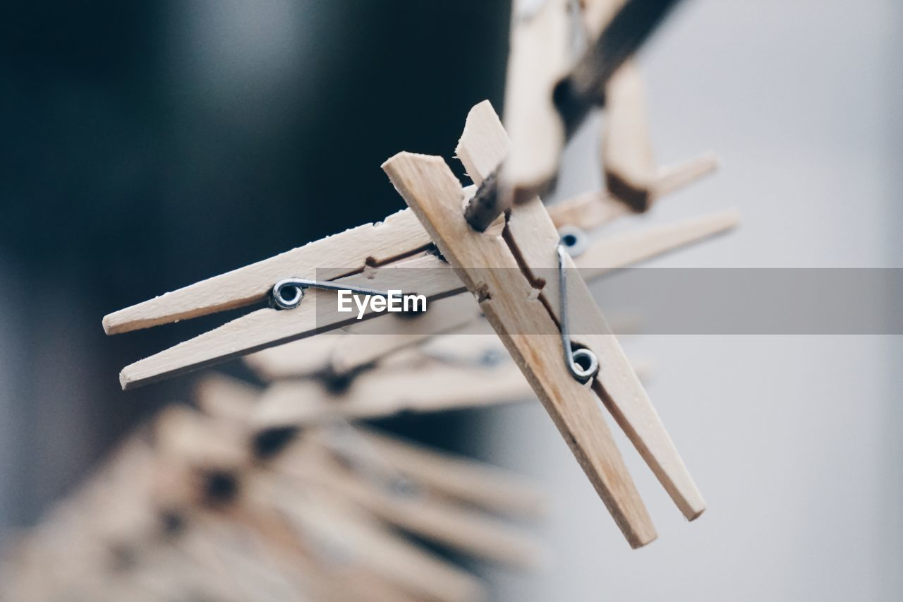 clothespin, selective focus, wood - material, close-up, no people, still life, metal, focus on foreground, equipment, clothesline, hanging, in a row, indoors, man made object, man made, group of objects, day, choice, sharp, table, silver colored