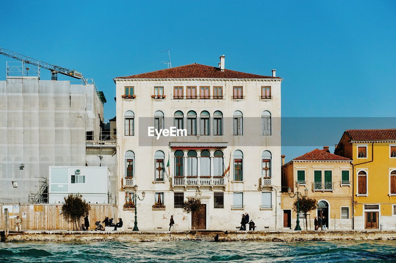 architecture, built structure, building exterior, water, sky, building, clear sky, nature, waterfront, day, city, window, residential district, sunlight, blue, outdoors, incidental people, arch, canal