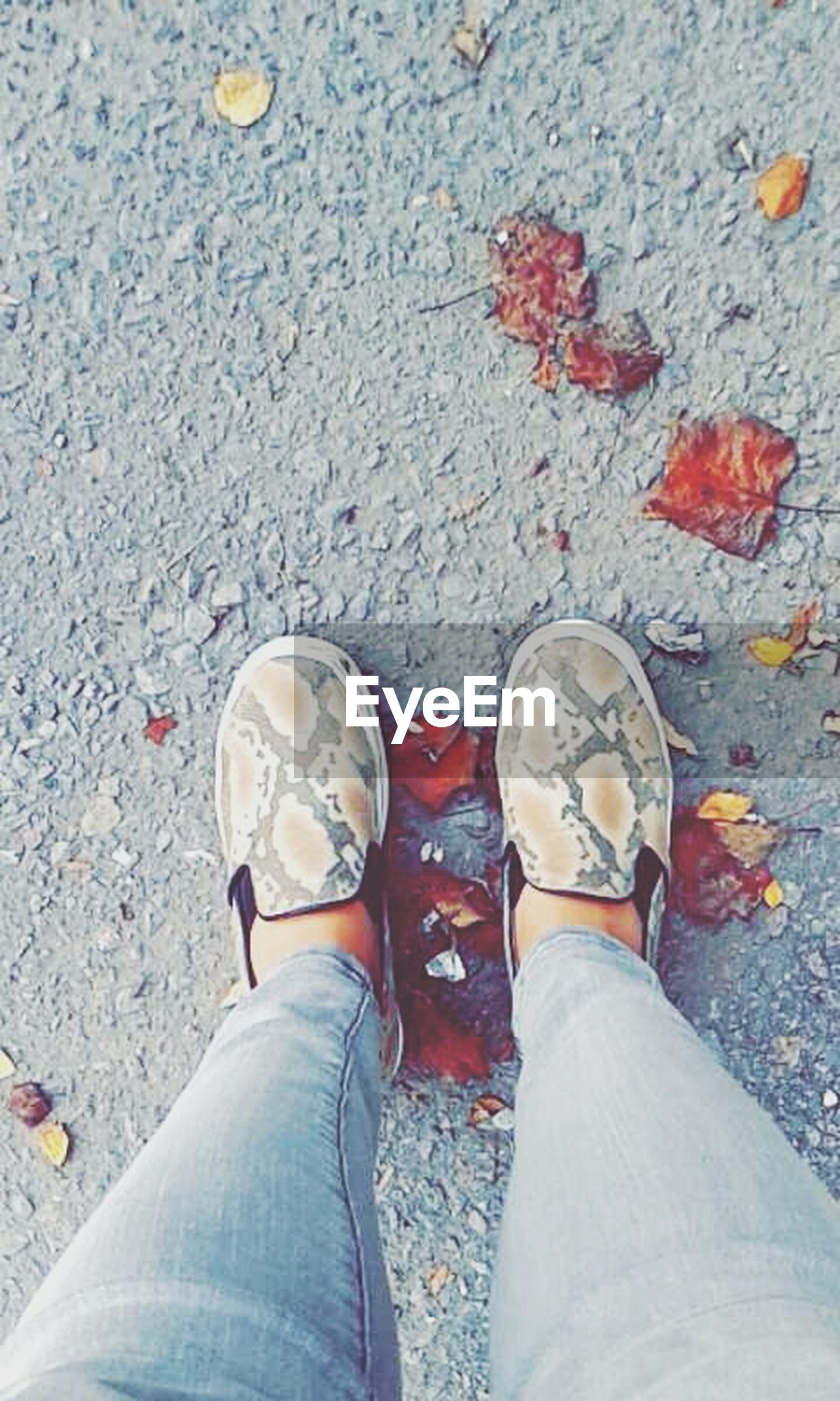 low section, person, shoe, personal perspective, standing, human foot, footwear, lifestyles, high angle view, jeans, men, leisure activity, directly above, street, casual clothing, canvas shoe