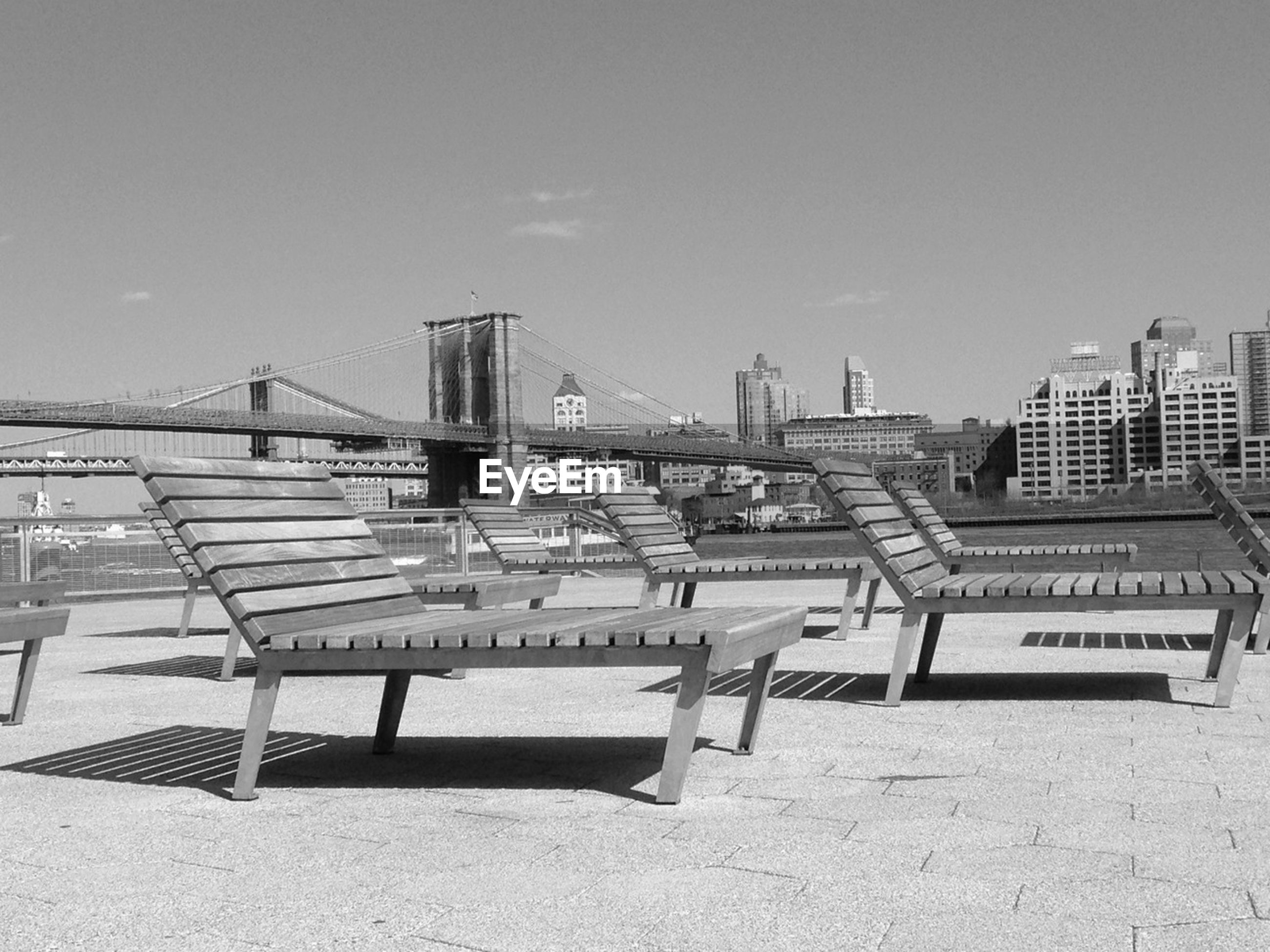 Empty deck chairs at river shore against sky