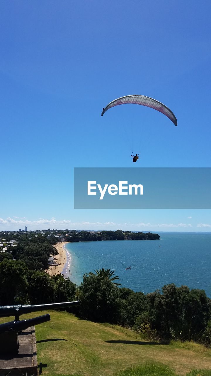 extreme sports, sport, adventure, sky, paragliding, parachute, plant, flying, unrecognizable person, mid-air, day, water, nature, beauty in nature, leisure activity, tree, joy, real people, sea, freedom, outdoors