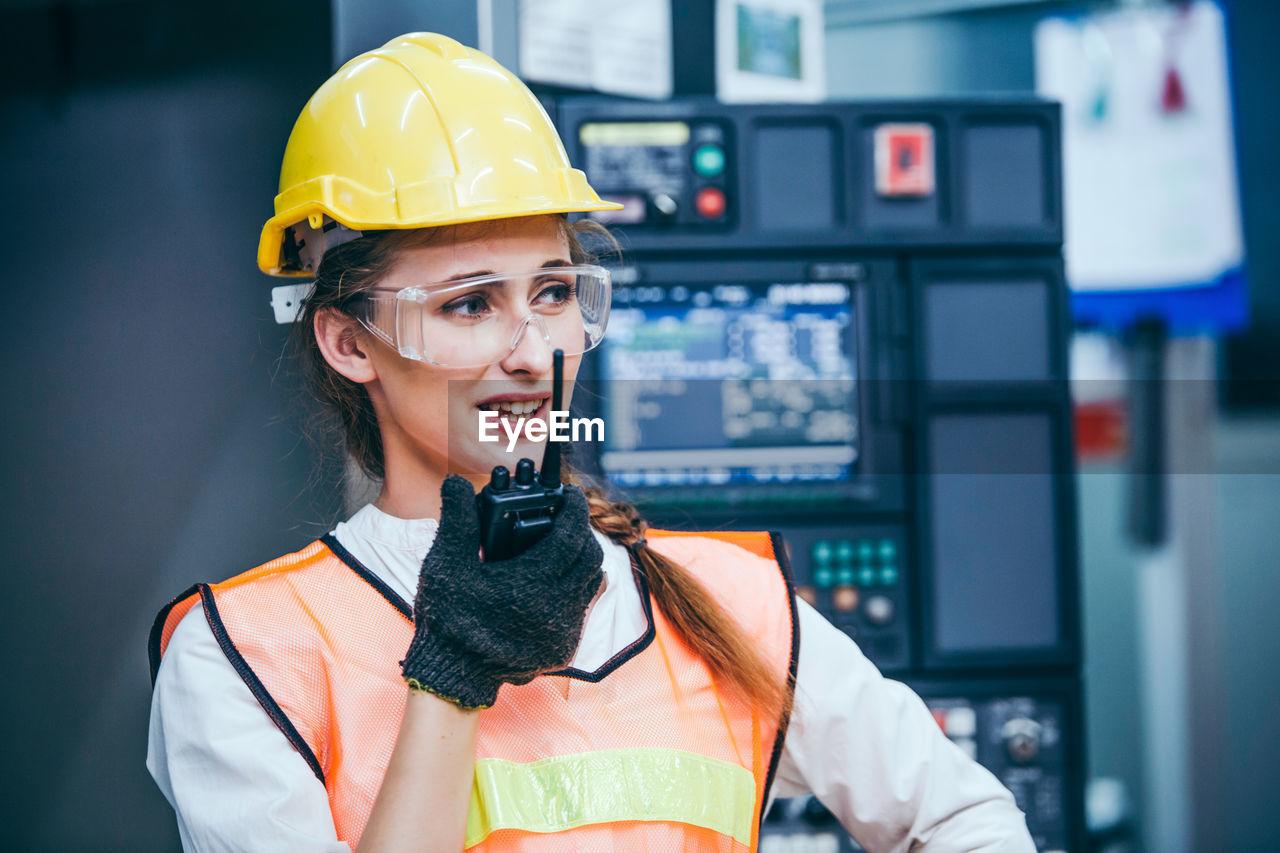 Young engineer talking on walkie talkie in factory