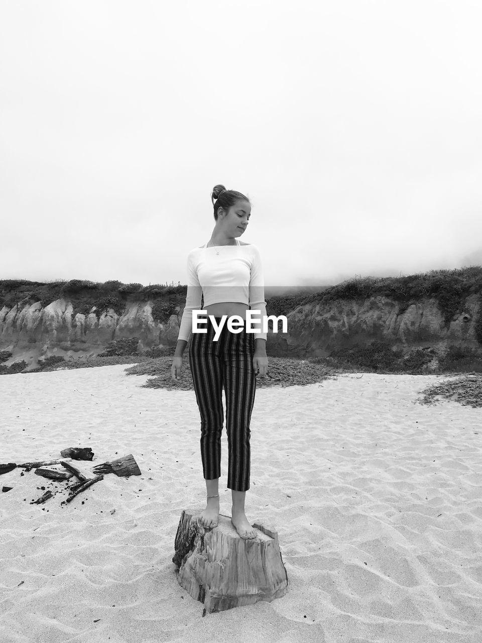 Full length of girl standing on tree stump at beach against sky