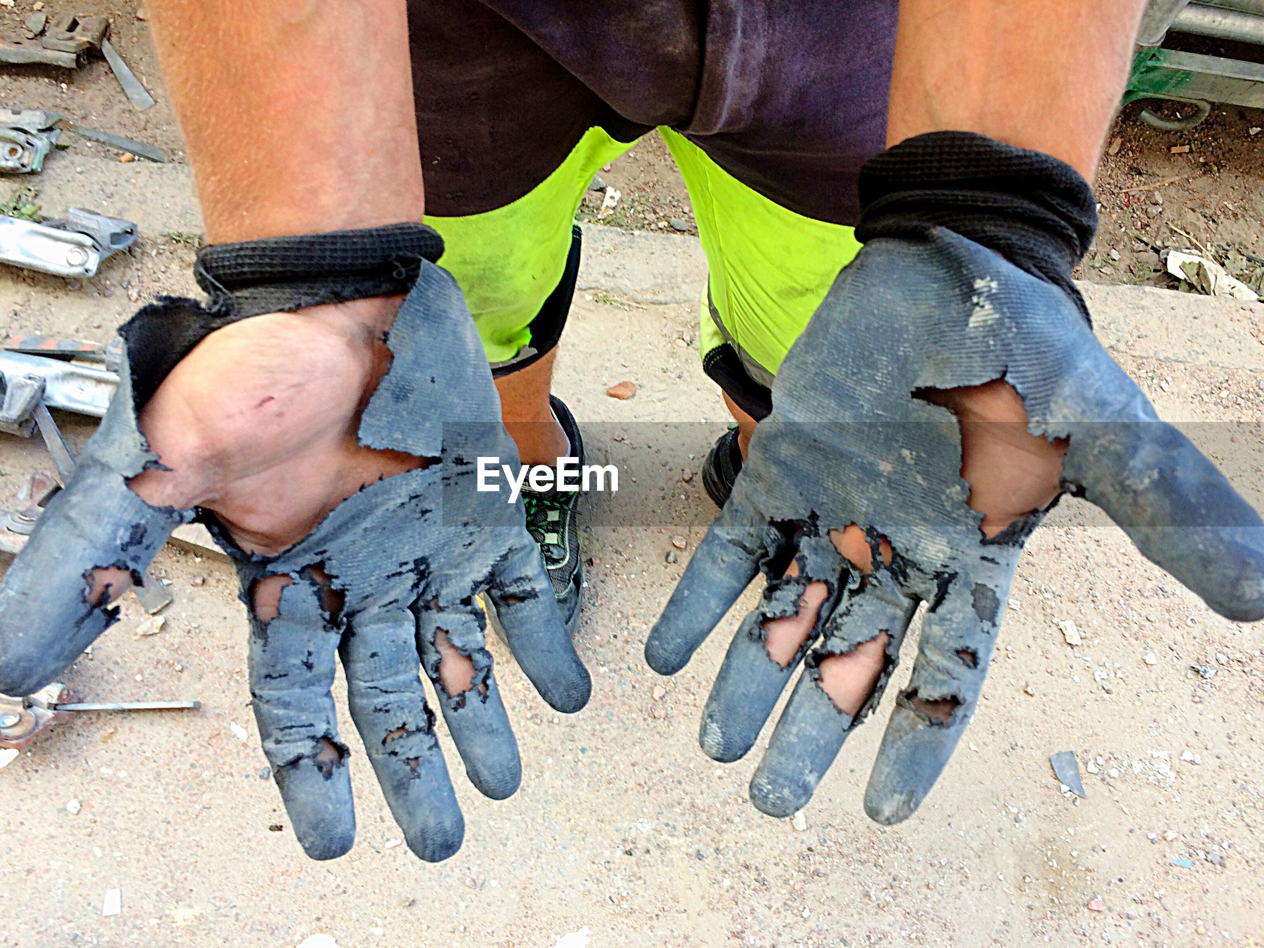 Low section of man wearing torn gloves while standing outdoors
