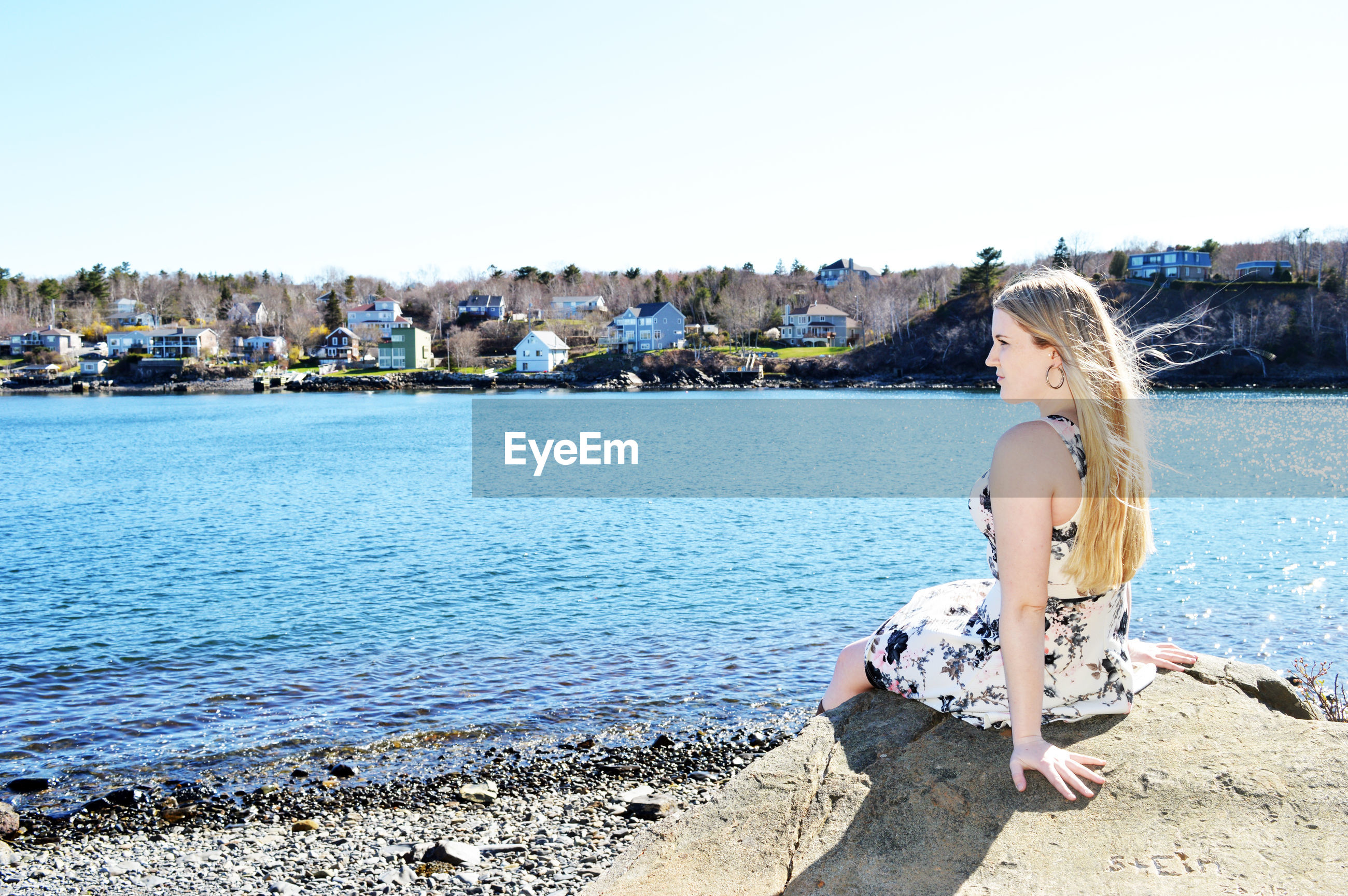Young woman sitting on rock at lakeshore against clear sky