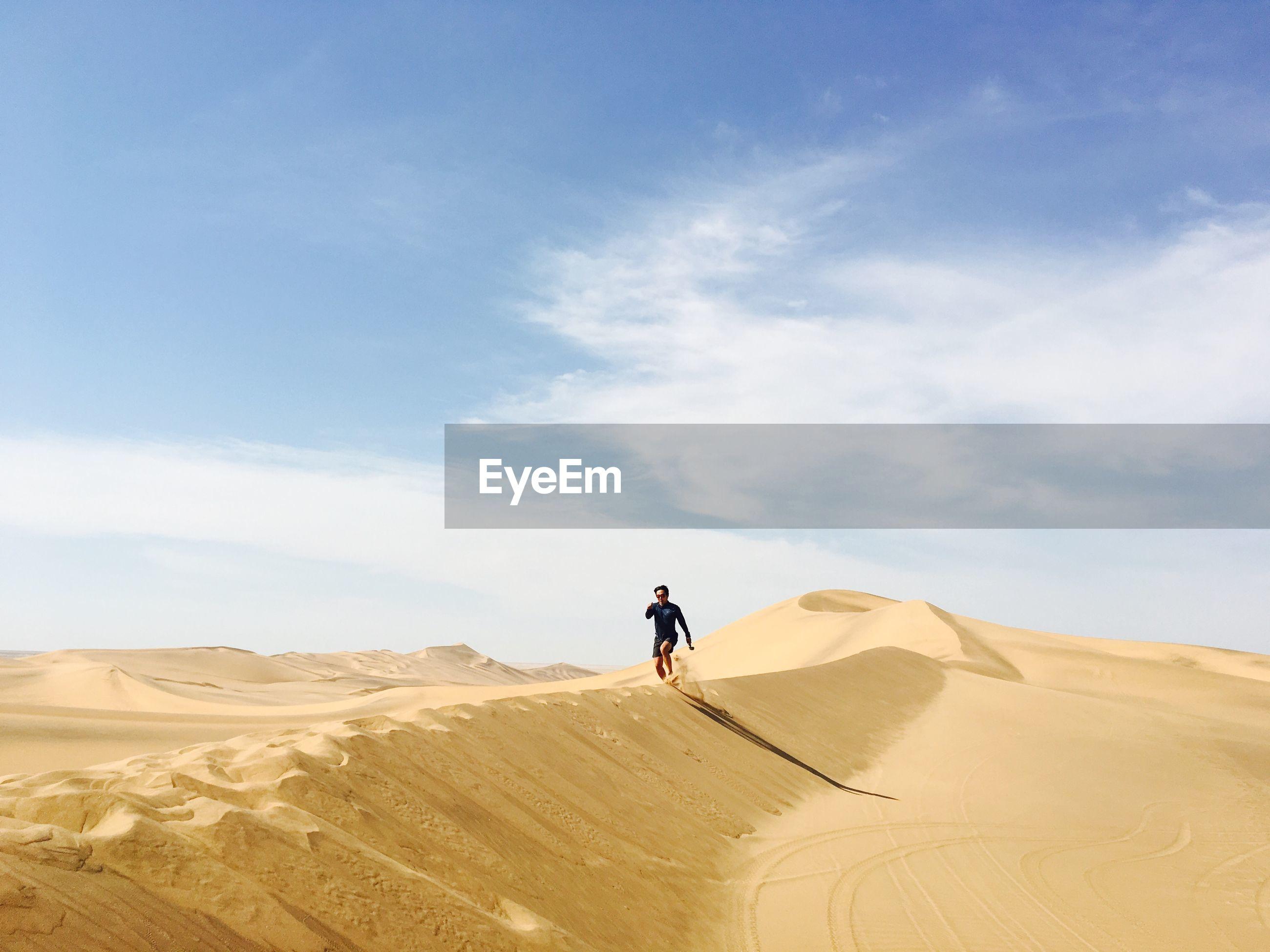 Young man running on desert against sky