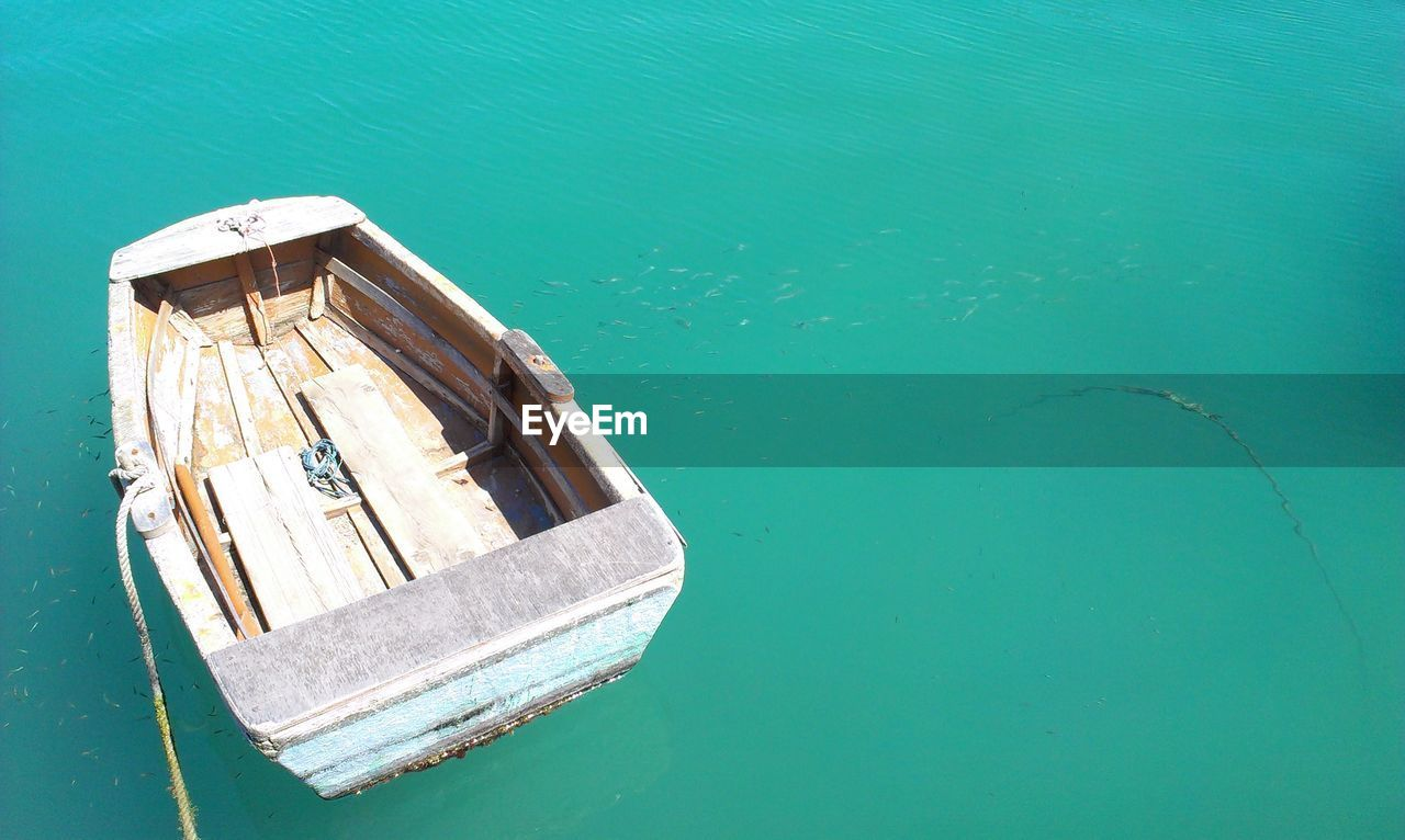 water, nautical vessel, no people, high angle view, sea, day, nature, transportation, mode of transportation, turquoise colored, wood - material, waterfront, outdoors, blue, tranquility, moored, built structure, sunlight, rowboat
