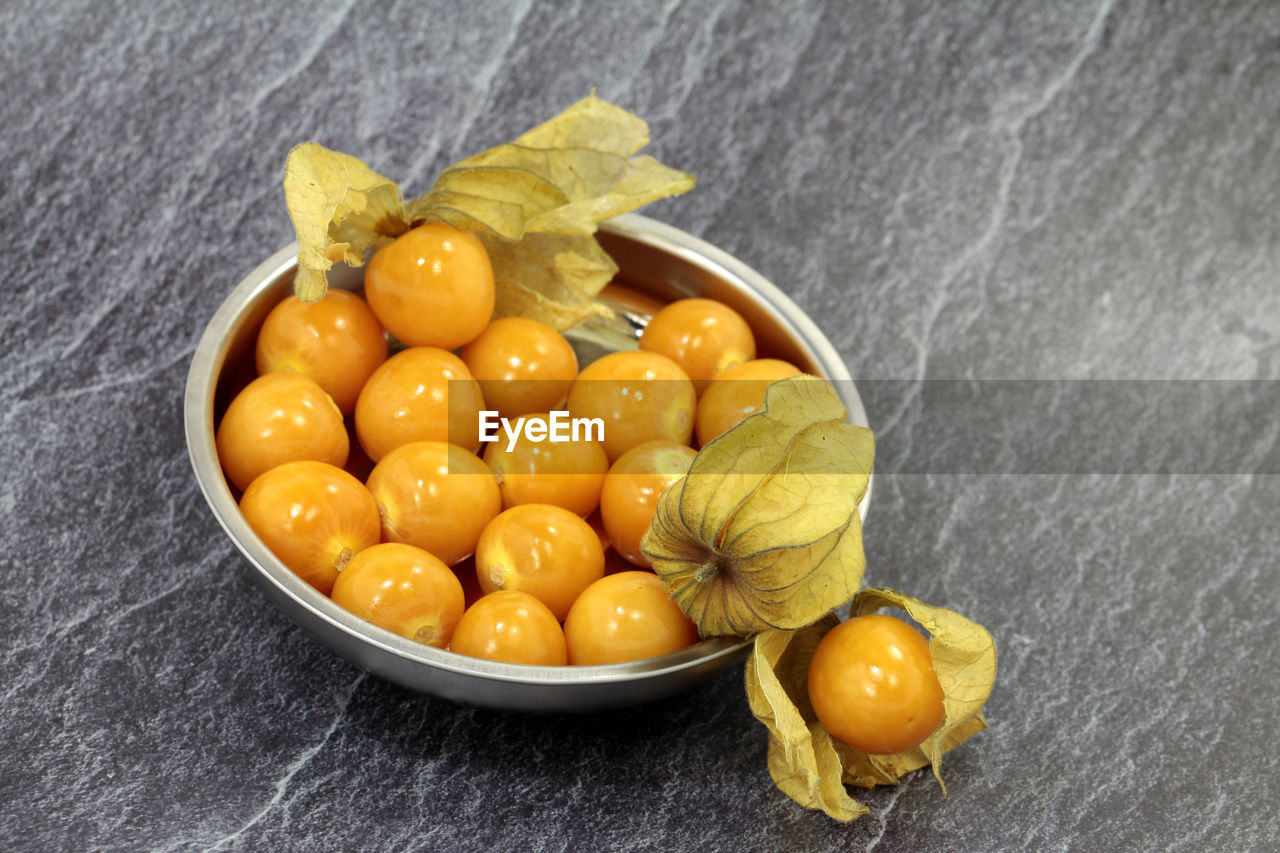 food, food and drink, healthy eating, fruit, freshness, yellow, wellbeing, indoors, close-up, no people, vegetable, citrus fruit, bowl, still life, high angle view, table, directly above, leaf, orange color, plant part, sweetcorn