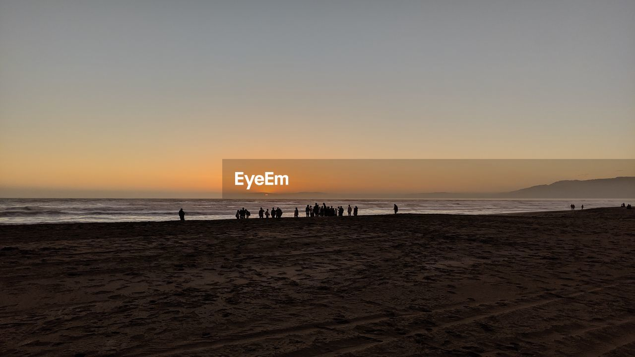 beach, sea, sunset, land, sky, water, scenics - nature, silhouette, beauty in nature, sand, group of people, copy space, horizon over water, tranquility, nature, real people, horizon, clear sky, tranquil scene, outdoors