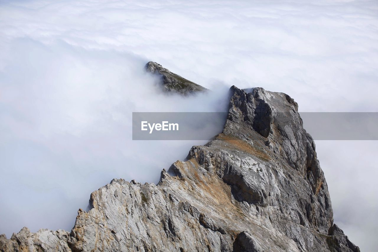High angle view of fog over rocky mountains