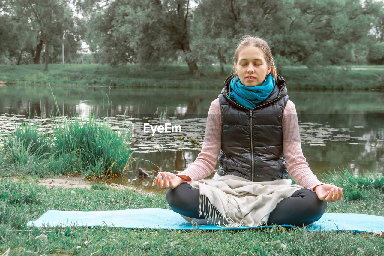 Young woman meditating in park. concept of mental health, wellness and reconnecting with nature.