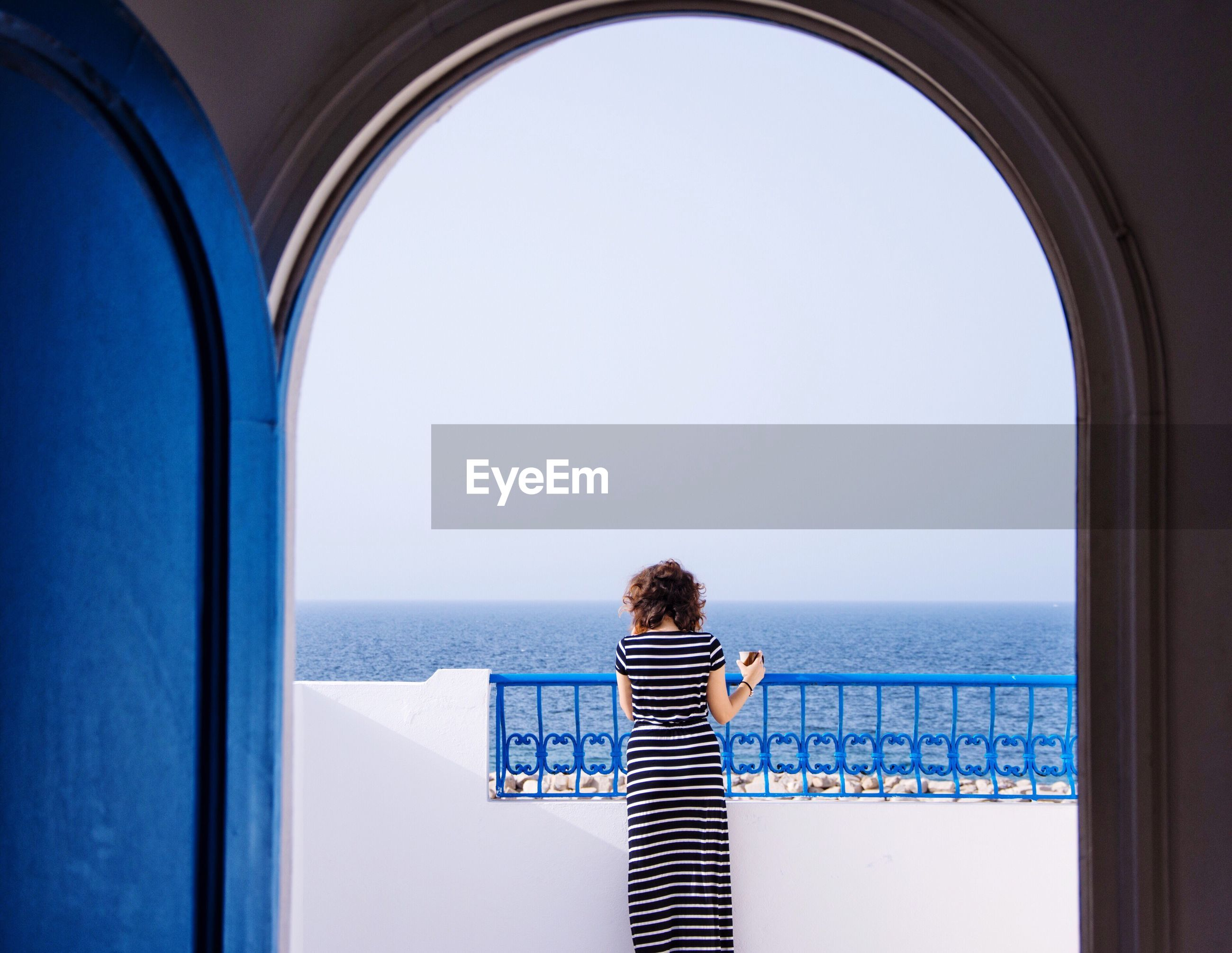 Rear view of woman with coffee cup standing in balcony against clear sky