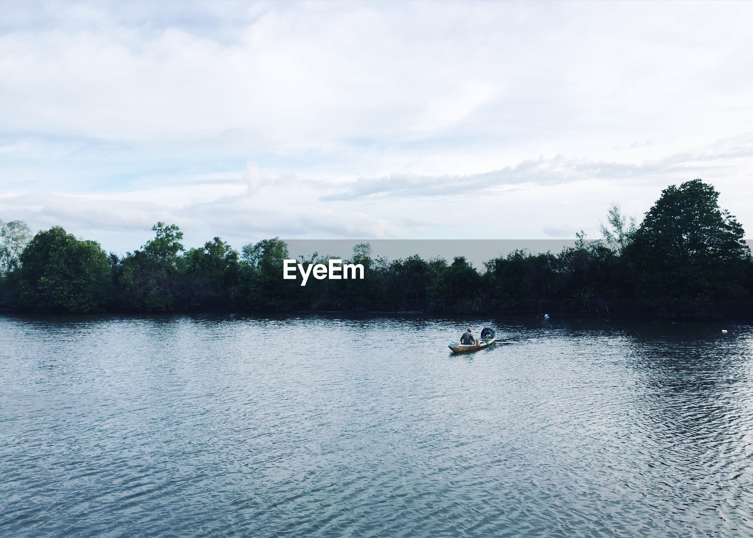 Man sitting on boat in river against cloudy sky