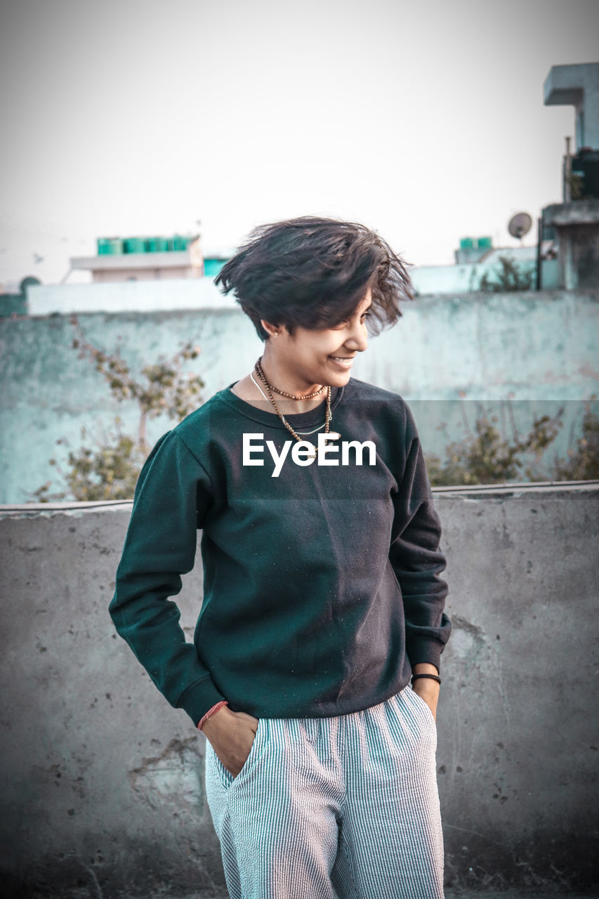 one person, three quarter length, real people, casual clothing, architecture, standing, built structure, building exterior, leisure activity, lifestyles, day, focus on foreground, front view, young adult, young men, outdoors, hair, hairstyle, adolescence, teenager, contemplation, teenage boys